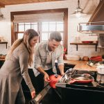 man and woman cooking with residential oven