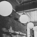 black and white image of lights in a brick restaurant